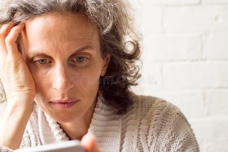 Женщина постаретая серединой используя телефон стоковое фото