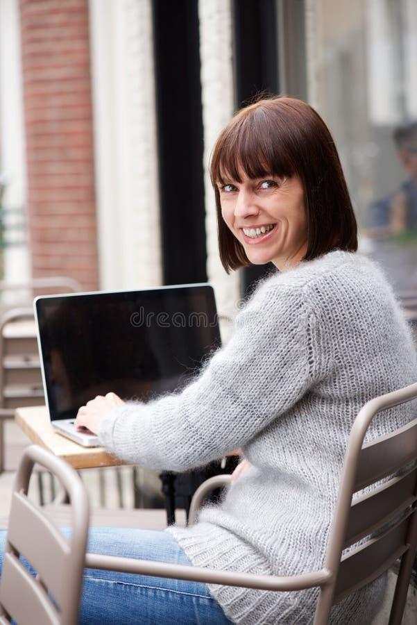 Женщина постаретая серединой сидя снаружи используя компьтер-книжку стоковые фотографии rf