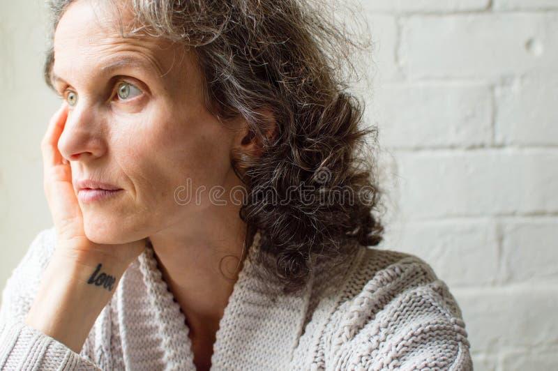 Женщина постаретая серединой смотря заботливый стоковое изображение rf