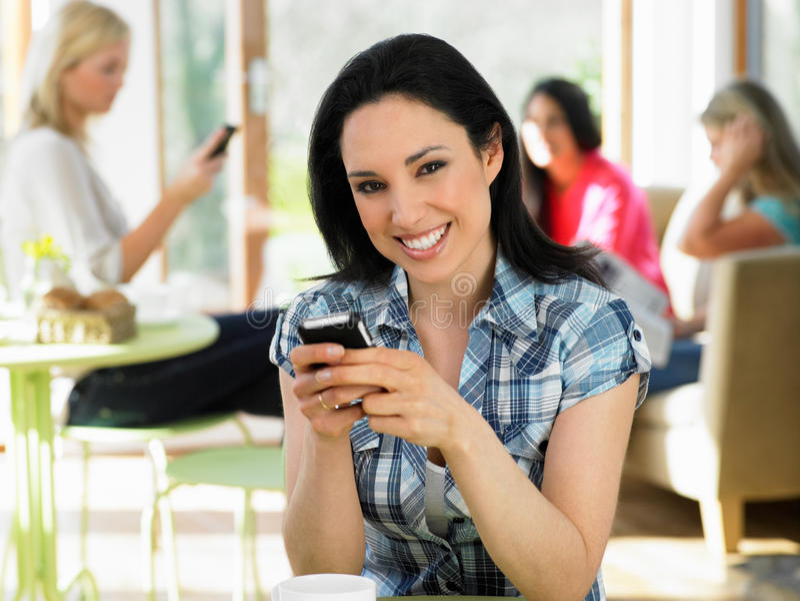 Женщина посылая текстовое сообщение в кафе стоковое фото