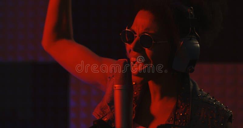 Женщина поя в записывая будочке стоковая фотография