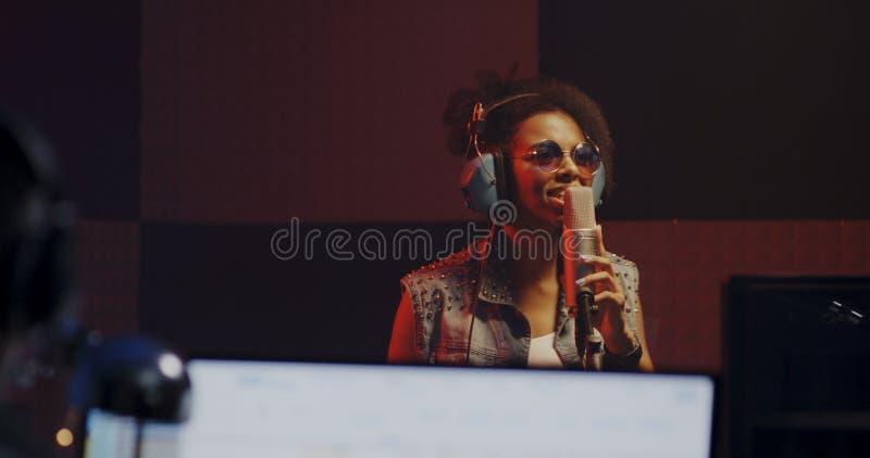 Женщина поя в записывая будочке стоковые фотографии rf