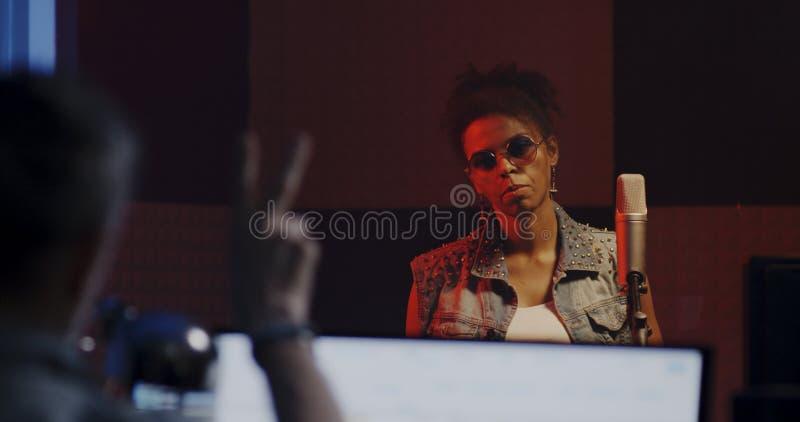 Женщина поя в записывая будочке стоковое изображение