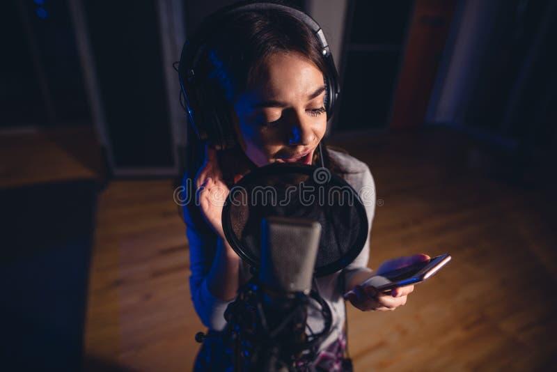 Женщина поя в студии звукозаписи стоковые фотографии rf