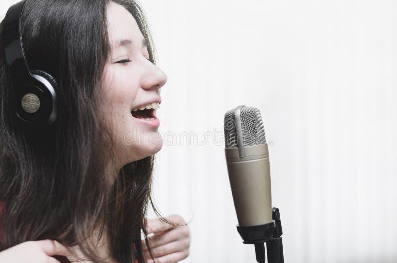 Женщина поя на микрофоне студии, нося наушники стоковое фото