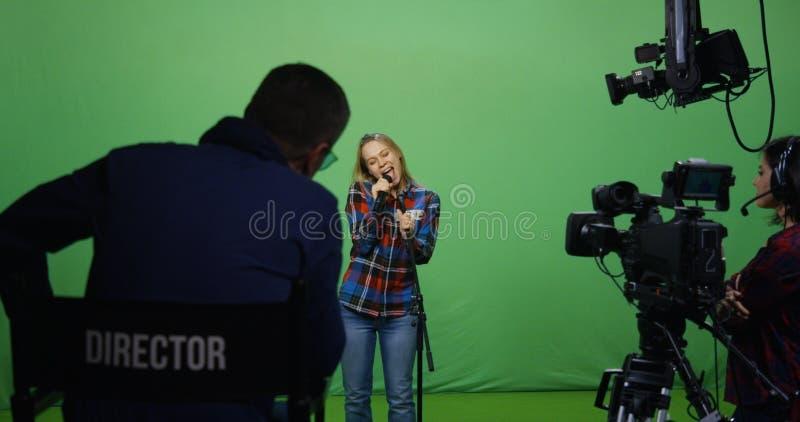 Женщина поя на прослушивании стоковое изображение