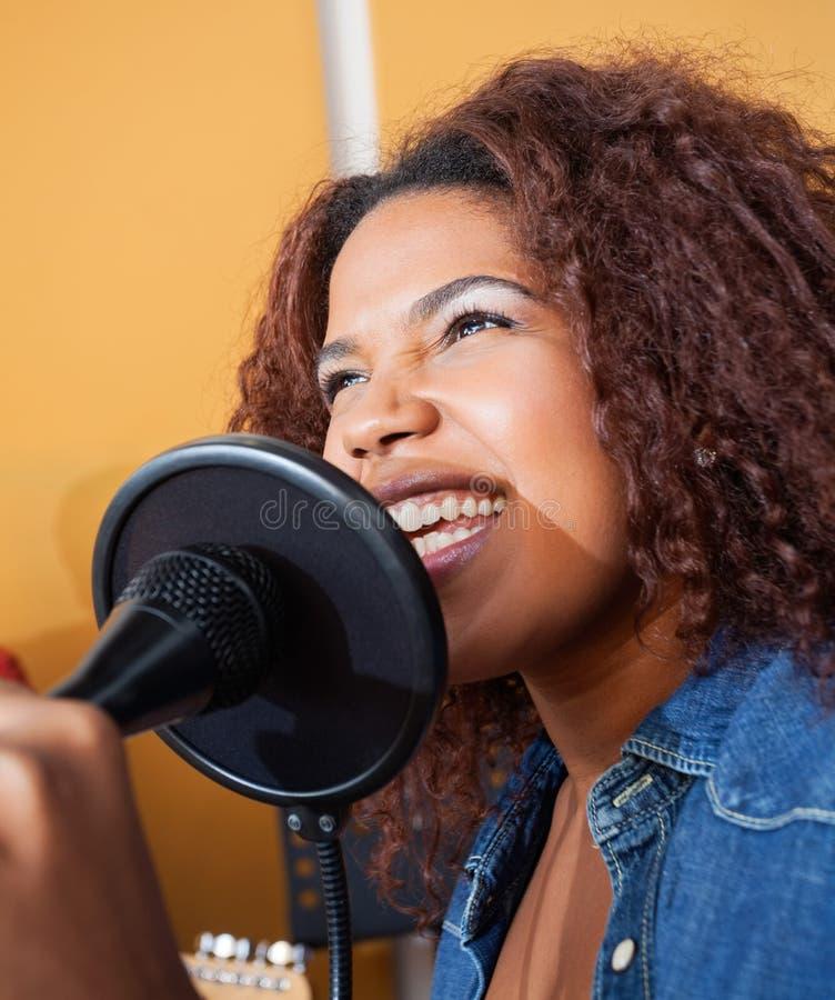 Женщина поя пока держащ микрофон внутри стоковое изображение