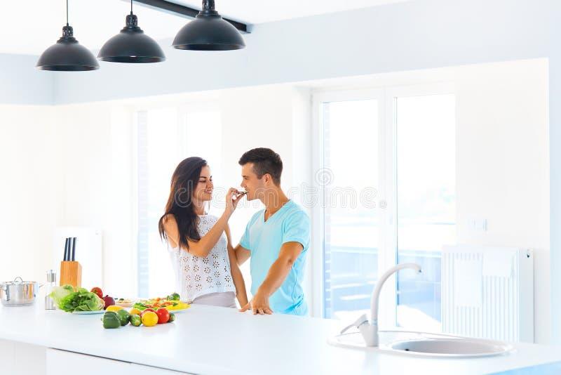 Женщина подавая ее человек в их кухне стоковое фото