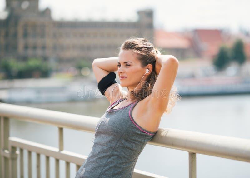 Женщина полагаясь назад с руками за головой, ослабляя на мосте стоковое фото rf