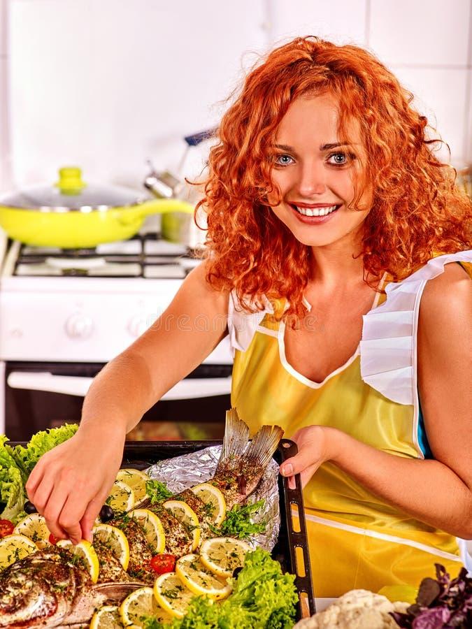 Женщина подготавливает рыб в печи стоковые изображения