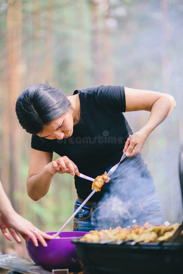 Женщина подготавливая мясо на гриле стоковое фото rf