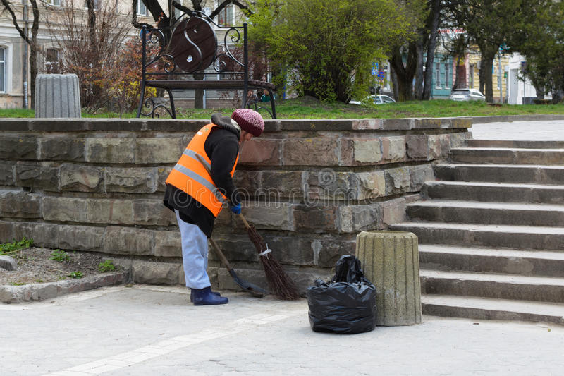Женщина подметает уборщика улицы стоковые изображения