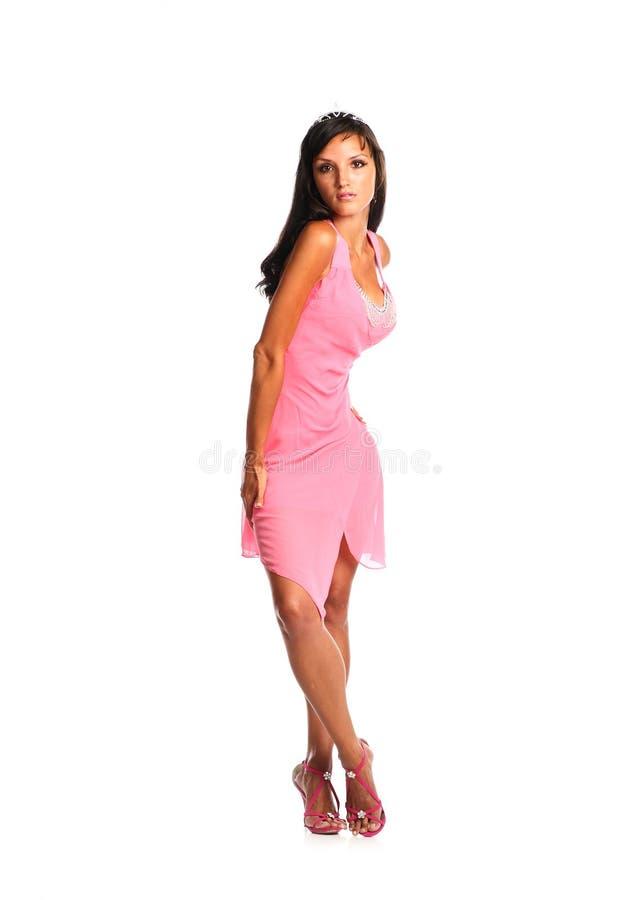Женщина подростка нося розовый представлять платья изолированный на белой предпосылке стоковое фото