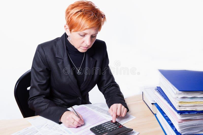 Женщина подсчитывает налоги стоковая фотография