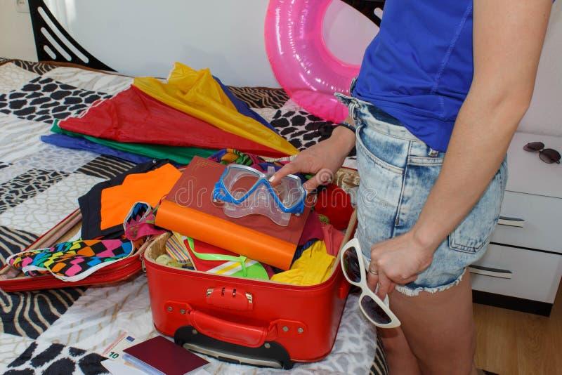 Женщина получая готовый для путешествовать Чемоданы упаковки молодой женщины на поле дома стоковые изображения rf