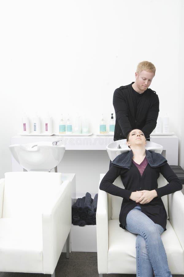 Женщина получая ей мытье волос в салоне стоковое фото rf