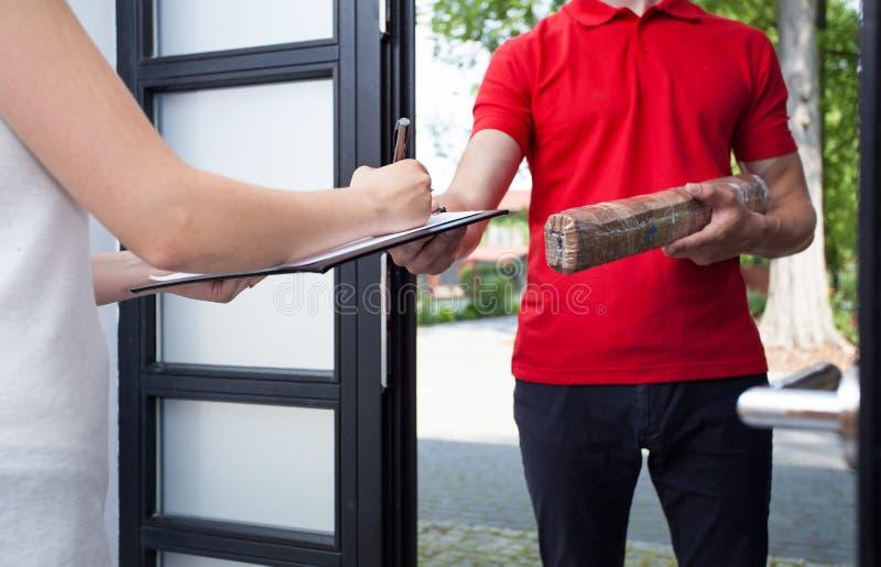 Женщина получая пакет от работника доставляющего покупки на дом стоковые фотографии rf