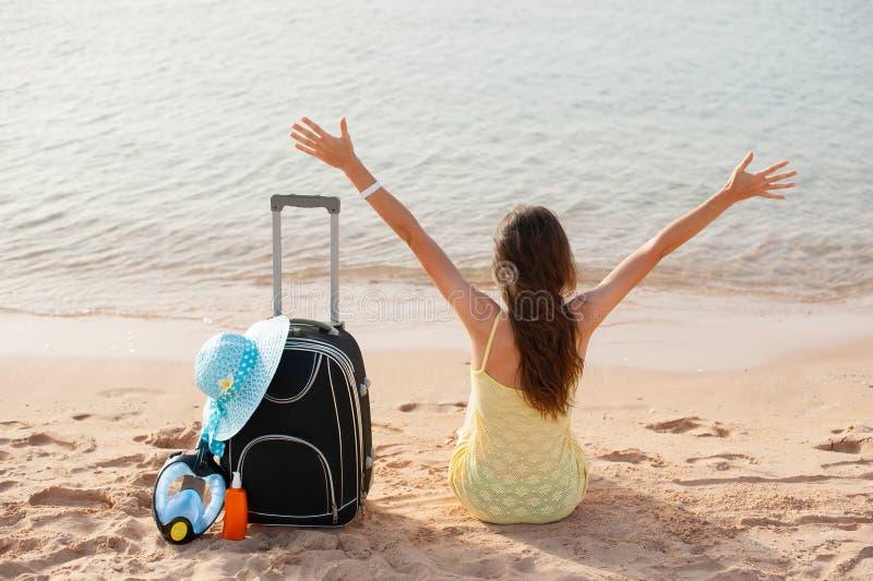 Женщина праздников пляжа наслаждаясь солнцем лета сидя в песке выглядя счастливый на космосе экземпляра Красивая молодая модель стоковая фотография