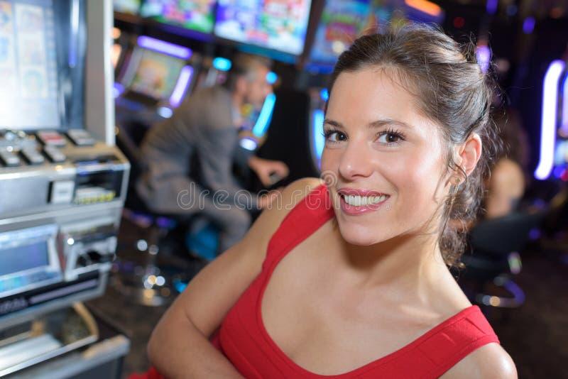 Женщина празднуя выигрыш на торговом автомате на казино стоковое фото rf