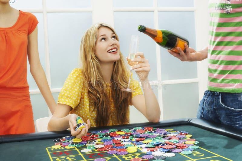 Женщина празднуя с подрезанными друзьями на таблице рулетки стоковые фотографии rf