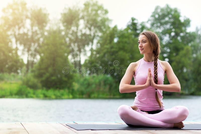 Женщина практикует йогу около реки Раздумье в природе r стоковое изображение rf