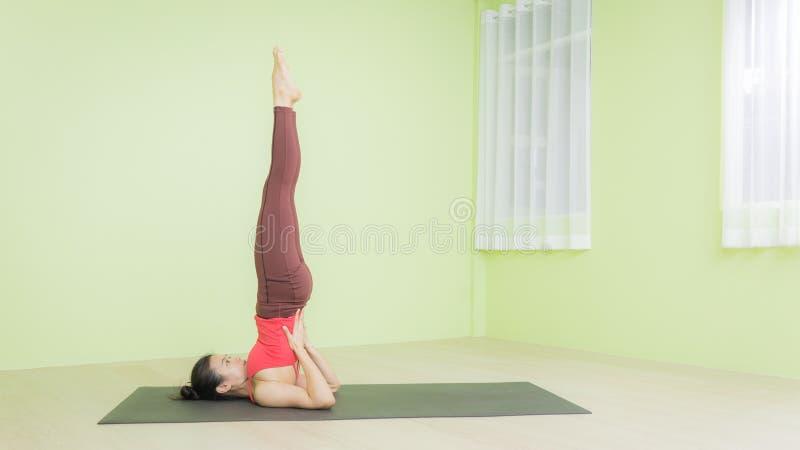 Женщина, практикующая йогу, позу для подставки стоковые изображения