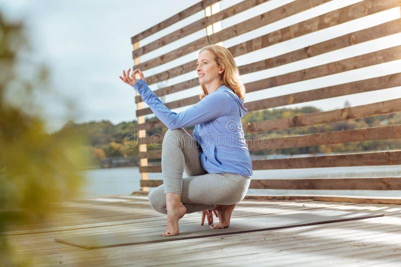 Женщина практикуя половинного лорда йоги рыб представляет на открытом воздухе стоковые фотографии rf