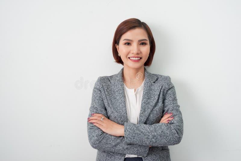 Женщина предпринимателя молодая азиатская, оружия бизнес-леди пересекла на белую предпосылку стоковые фото