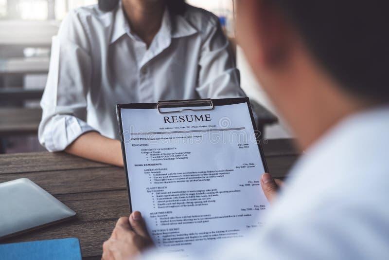 Женщина представляет заявление о приеме на работу, интервьюера читая резюме стоковые фотографии rf