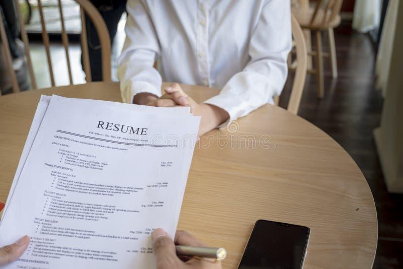 Женщина представляет заявление о приеме на работу, интервьюер читая резюме стоковые изображения