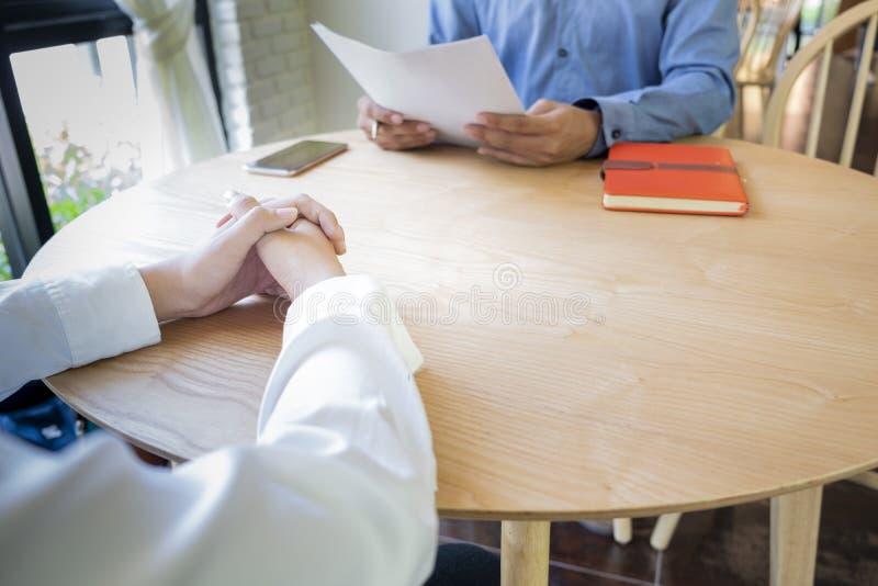 Женщина представляет заявление о приеме на работу, интервьюер читая резюме стоковые фото