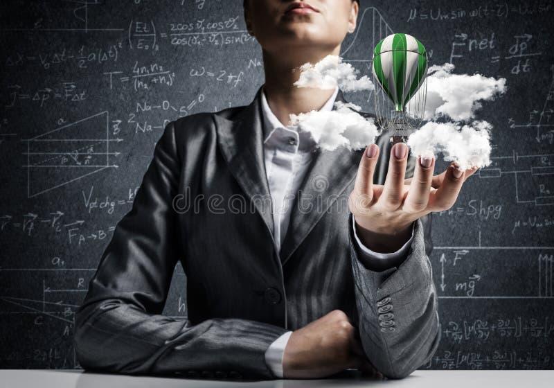 Женщина представляя воздушный шар летания в руке стоковое фото rf