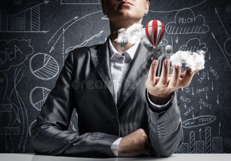 Женщина представляя воздушный шар летания в руке стоковое изображение rf
