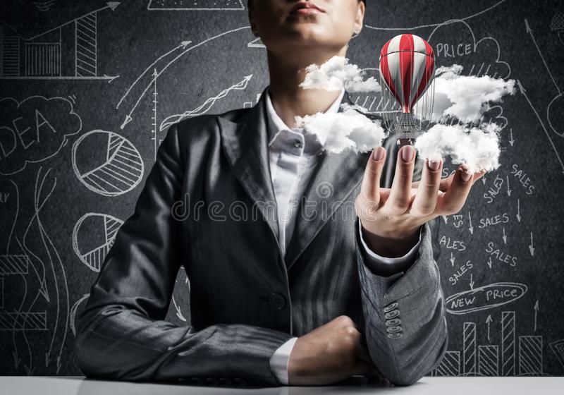 Женщина представляя воздушный шар летания в руке стоковые изображения