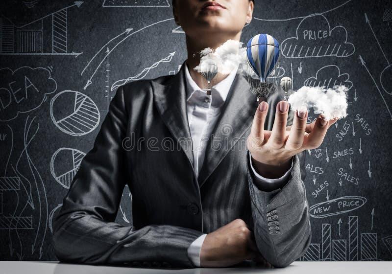 Женщина представляя воздушный шар летания в руке стоковое изображение