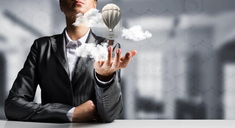 Женщина представляя воздушный шар летания в руке стоковые фото