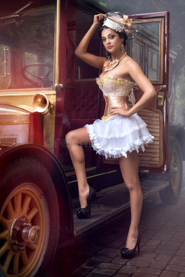 Женщина представляя над ретро автомобилем стоковые фотографии rf