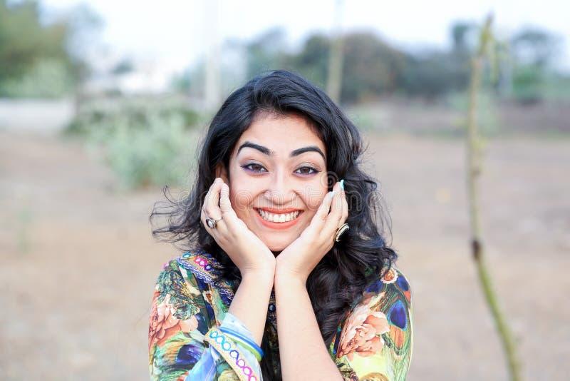 Женщина представляя счастливые руки улыбки на стороне стоковое фото rf