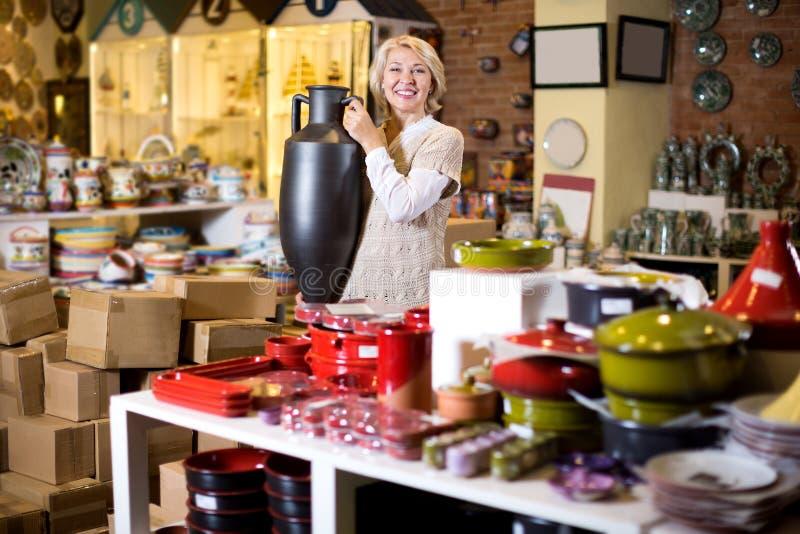 Женщина представляя с керамическим tableware стоковые изображения