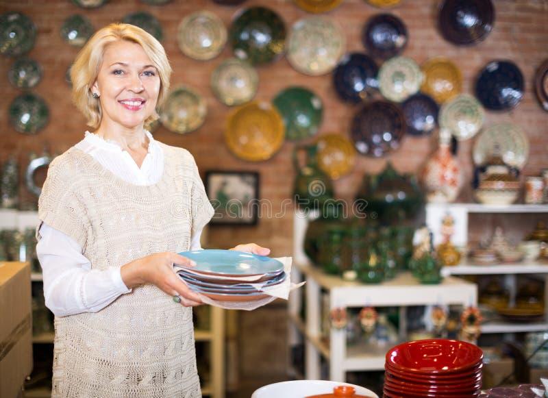 Женщина представляя с керамическим tableware стоковое изображение rf