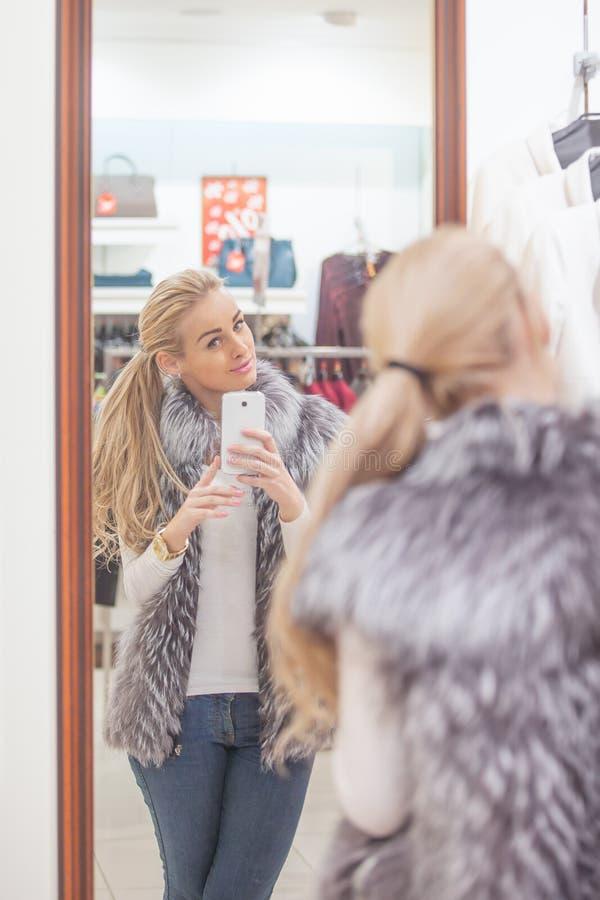 Женщина представляя для selfie с умным телефоном, стоковая фотография rf