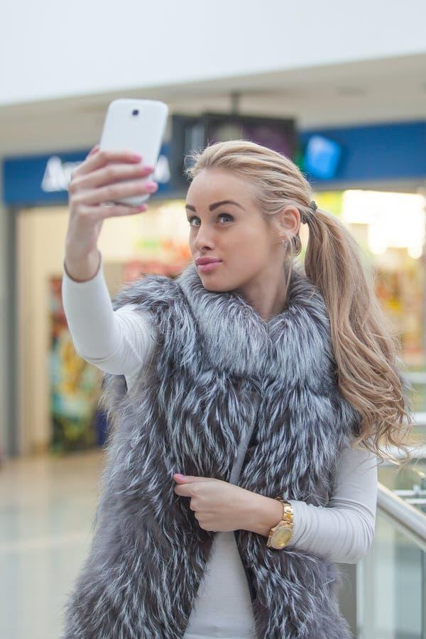 Женщина представляя для selfie с умным телефоном стоковое изображение rf