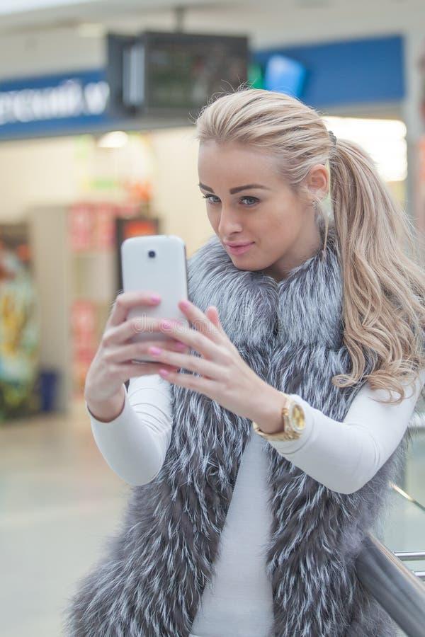 Женщина представляя для selfie с умным телефоном, стоковое изображение rf