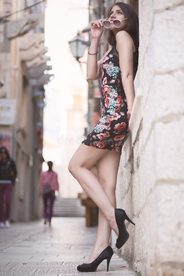 Женщина привлекательного брюнет элегантная имея потеху наслаждаясь летом, смеяться над и усмехаться счастливым во время перемещен стоковые фото