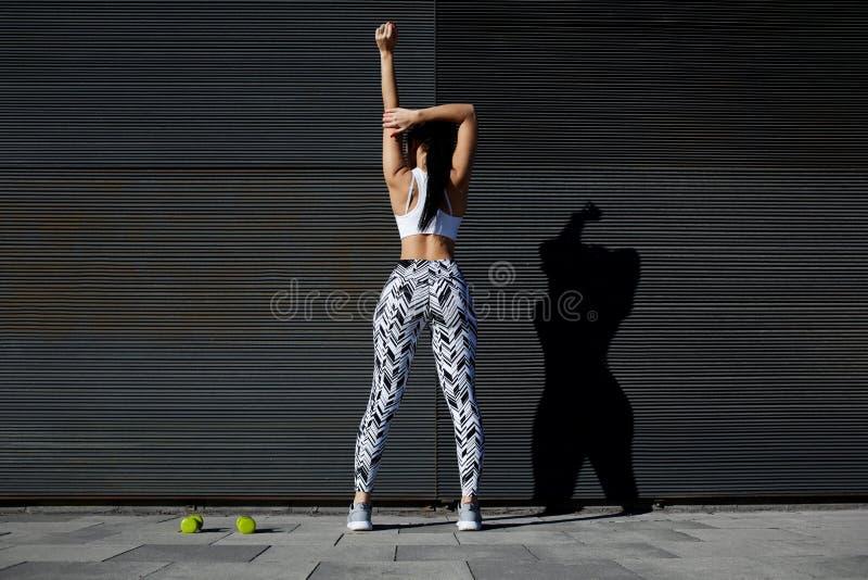 Женщина пригонки в sportswear работая на черной предпосылке outdoors стоковые фотографии rf