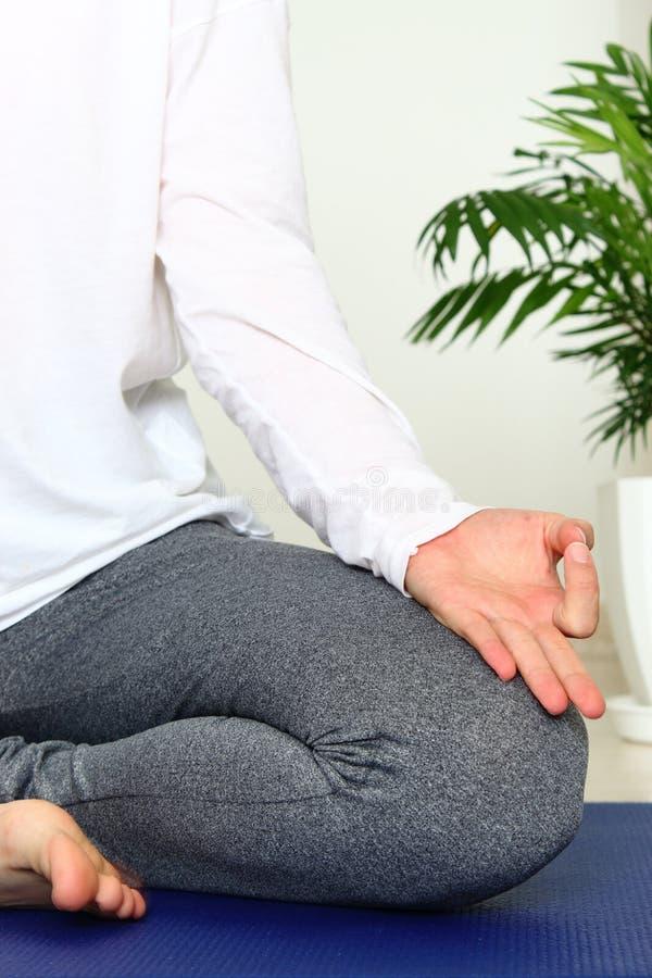 Женщина пригонки делая йогу на циновке дома Молодая женщина размышляя внутри помещения Раздумье йоги дома принципиальная схема ос стоковая фотография rf