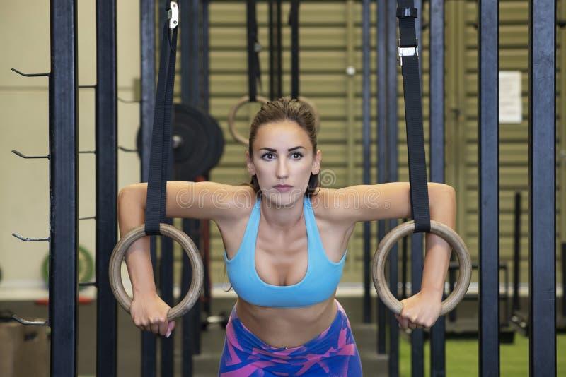 Женщина пригонки работая с кольцами гимнастики на спортзале, оздоровительном клубе или студии фитнеса стоковое изображение rf