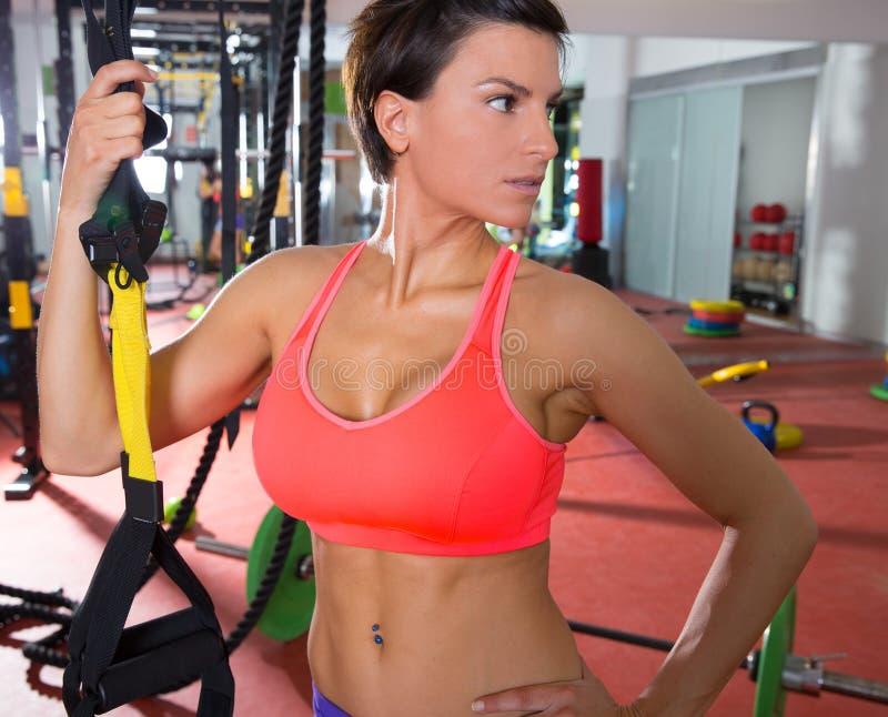 Женщина пригодности Crossfit стоя на спортзале держа trx стоковые изображения