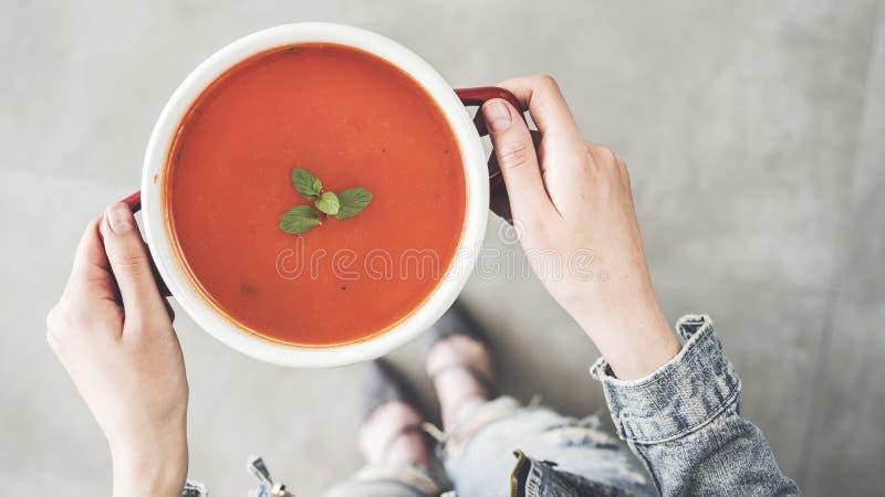 Женщина придерживаясь взгляда высокого угла бака супа томата стоковые изображения rf