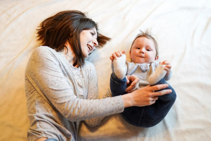 Женщина прижимаясь с ее прелестным младенцем, сладкий ребенк усмехаясь на камере стоковое фото
